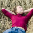 Girl lays on a dry grass — Stock Photo #5648736