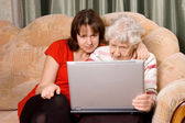 Family on a sofa with computer — Stock Photo