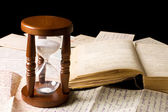 Hourglass on old letters — Stock Photo