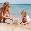 Mother with the child playing with sand on beach — Stock Photo