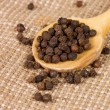 Black Peppercorns on a wooden spoon - Stock Photo