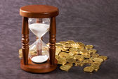 Hourglasses and coin on a grey — Stock Photo