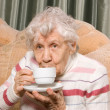 Grandmother from coffee on a sofa — Stock Photo