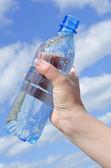 Botella de agua en una mano contra el cielo — Foto de Stock