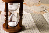 Hourglass on old letters — Stockfoto