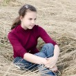 Stock Photo: Girl Sits on dry grass