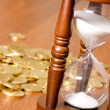 Hourglasses and coin On wooden table - Stock Photo