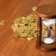 Hourglasses and coin On wooden table — Stock Photo #6141262