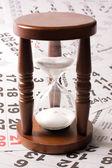 Hourglass on calendar sheets — Stock Photo