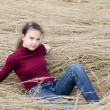 Girl lays on a dry grass — Stock Photo