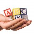 Hand holds a cube with letters — Stock Photo