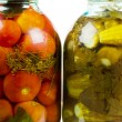 图库照片: Jars of pickles and tomatoes