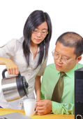 Office worker serving coffee to a man — Stock Photo