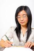 Chinese businesswoman, sitting at desk writing — Stock Photo