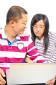Young chinese couple sitting with a laptop — Stock Photo