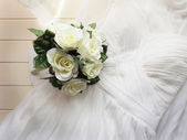 Wedding gown and bouquet — Stock Photo
