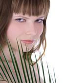 ładna twarz kobiety, chowając się za dużych liści zielony — Zdjęcie stockowe