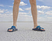Tanned legs of man wearing flip flops standing on the beach — Stock Photo