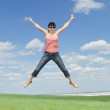 Pretty young woman jumping on green grass over blue sky — Stock Photo #5982504