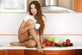 Beautiful caucasian woman in the kitchen. — Stock Photo