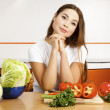 Stock Photo: Beautiful caucasian woman preparing salad in the kitchen.