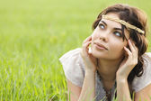 Young brunette woman is laying in the grass looking up — Stock Photo