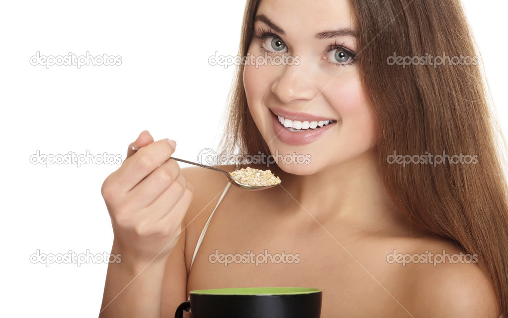 Portrait of young caucasian woman eating cereals, isolated over white background. — Stock Photo #5896680