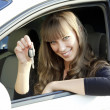 Cheerful young lady sitting in a car and showing key — ストック写真