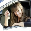 Cheerful young lady sitting in a car and showing key — Stock fotografie