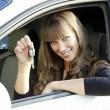allegra signora giovane seduto in una macchina e mostrando la chiave — Foto Stock