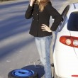 Young woman standing by her damaged car and calling for help — Stock Photo #5906495