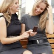 Two smiling girls watching something in mobile phone — Stock Photo #5907815
