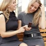 Две улыбаясь девочки смотрят что-то в мобильном телефоне — Стоковое фото