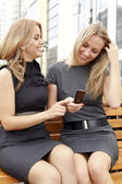 Two smiling girls watching something in mobile phone — Stock Photo