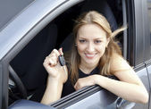The happy woman showing the key of her new car. — Stock Photo