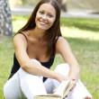 Beautiful woman reading a book at the park — Foto Stock