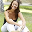 Beautiful woman reading a book at the park — Stockfoto
