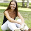 Foto Stock: Beautiful caucasian woman reading a book at the park