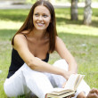 Beautiful caucasian woman reading a book at the park — Stok fotoğraf
