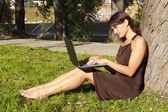 Woman sitting in park with a laptop — Stock Photo