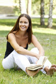 Beautiful caucasian woman reading a book at the park — Stock Photo