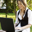 Young pretty woman with laptop sitting on the bench in a park — Stock Photo #6035029