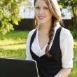 Young pretty woman with laptop sitting on the bench in a park — Stock Photo