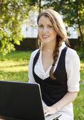 Giovane donna abbastanza con portatile seduto sulla panchina in un parco — Foto Stock