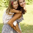 Stock Photo: Mother giving daughter piggy back ride at summer park