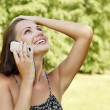 Laughing young woman talking on mobile phone — Stockfoto