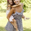 Mother giving daughter piggy back ride at summer park. — Stock Photo