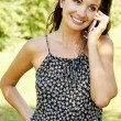Laughing young woman talking on mobile phone — Stock Photo