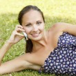 Girl with a mobile phone laying on a grass — Stock Photo