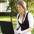 Young pretty woman with laptop sitting on the bench in a park — Stock Photo #6062186